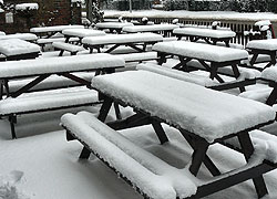 A photo of outdoor picnic seats covered in snow at the Thieves Neck pub in Woodford, Cheshire taken by Kris Hayward